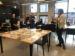 Présentation de Julie Ravary devant un groupe de gens, elle parle de documents qui sont disposés devant elle sur une table dans la salle de lecture d'Artexte.